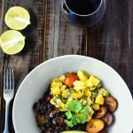 Vegan Black Bean Bowl on dark wood background with a glass of red wine and lime sliced in half.