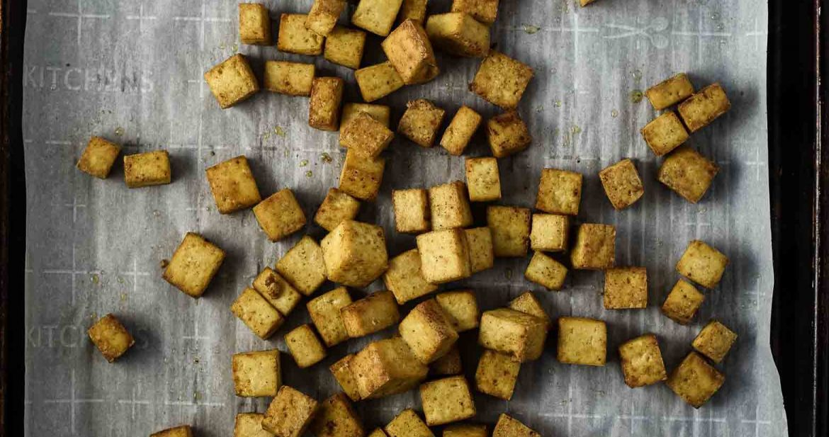 Crispy tofu recipe after coming out of the oven. The tofu is golden-brown and is sitting on parchment paper on a distressed cooking sheet.