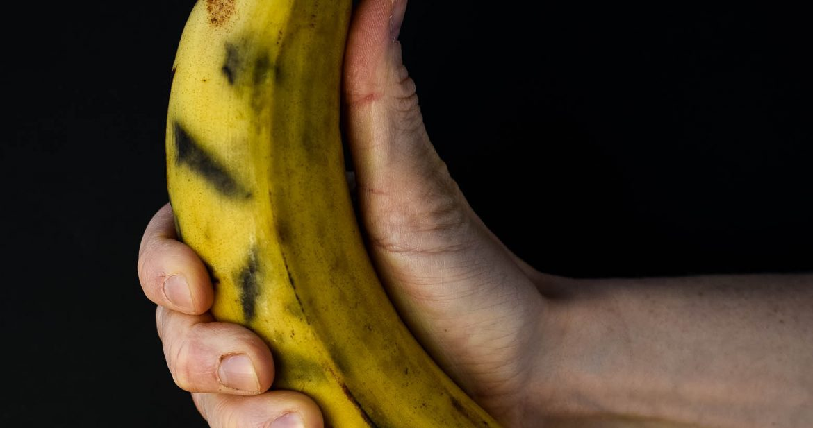 Plantain held in hand in front of black background. This plantain is for a fried plantain recipe.
