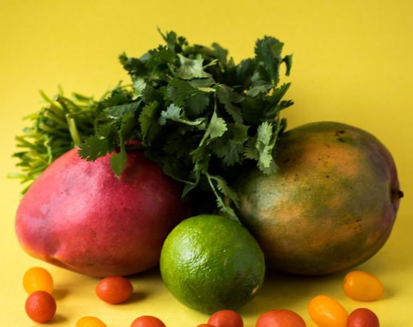 Fresh mango salsa ingredients sitting on a bright yellow background. There are two mangos, one lime, lots of cherry tomatoes, and cilantro stacked artfully like a still life.