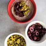 Red bowl has olive hummus in it, with two small white bowls that contain clopped kalamata and green olives on a textured grey background.