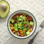 Black bean corn salad recipe in a white bowl with a green rim. There is a silver fork to the right of the bowl and a halved avocado and lime to the left of the bowl.