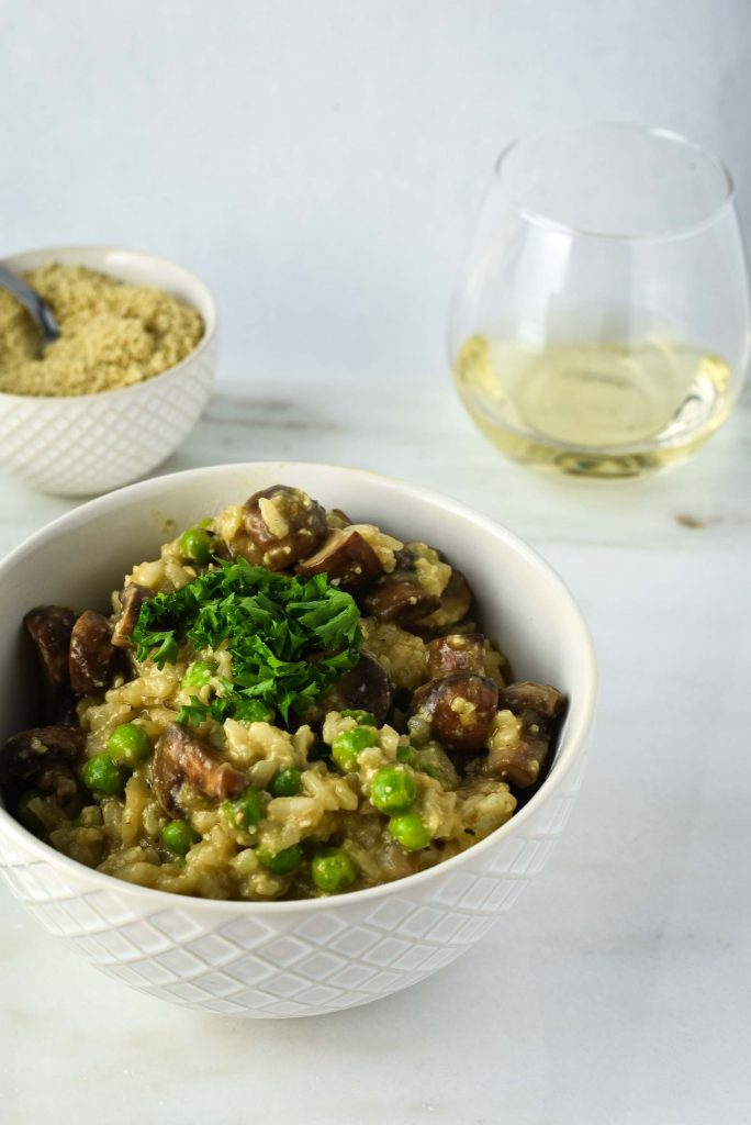 Vegan mushroom risotto in white textured bowl with vegan parmesan cheese in white bowl and white wine on white background.