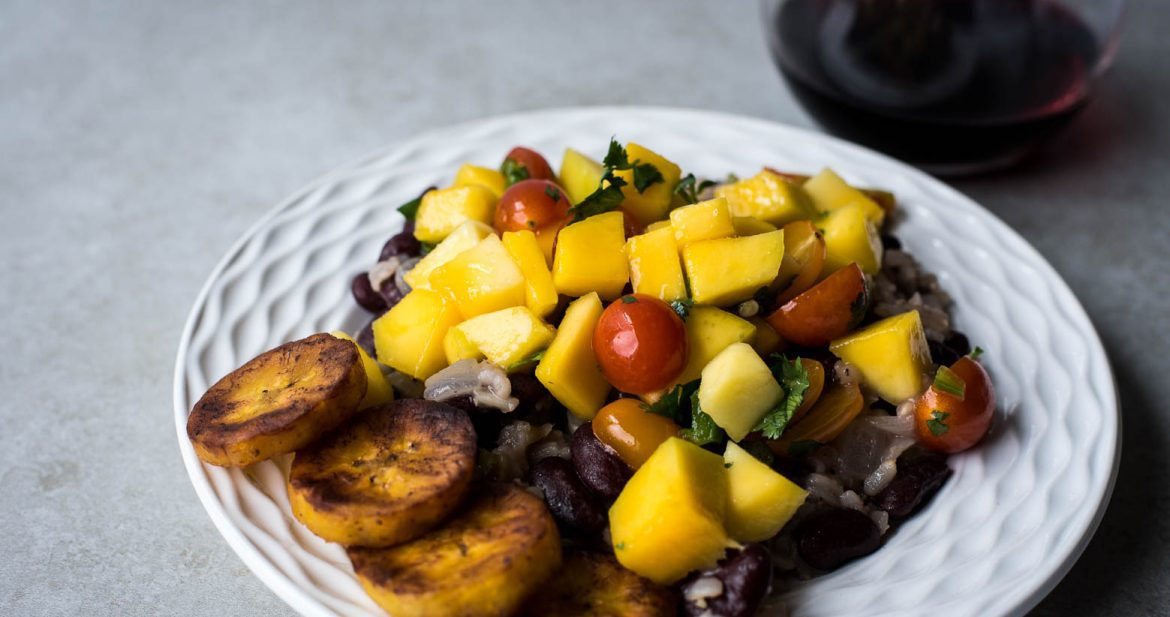 Gallo pinto prepared on a white plate with fresh mango salsa and fried plantains. There is a glass of red wine in the corner. Everything is sitting on a textured light grey background.