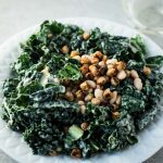 Kale Salad with Roasted Chickpeas on a white place with a glass of white wine.