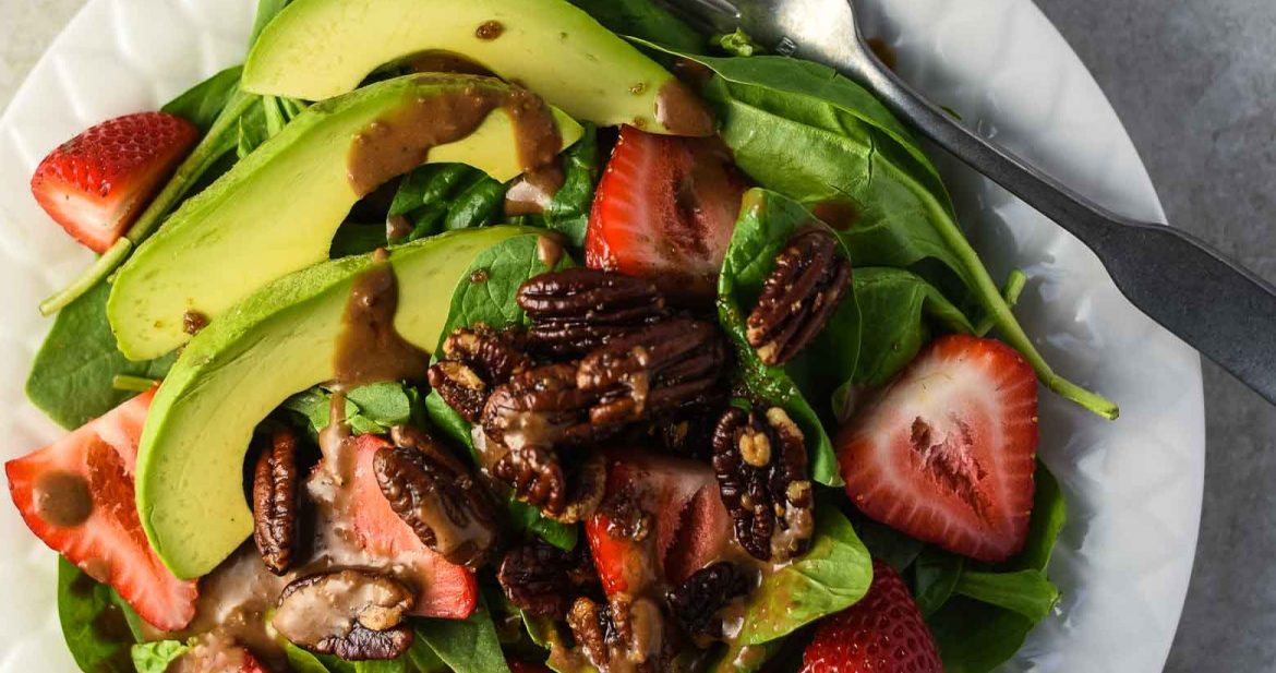 Strawberry spinach salad recipe on a white plate with a glass of rose wine. There is spinach, strawberries, avocados, candied pecans, and balsamic dressing.