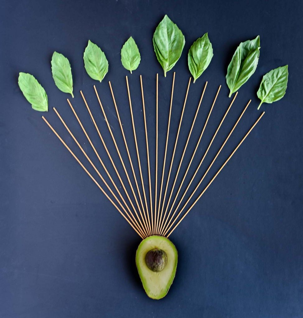 Avocado pasta recipe ingredients - avocado, spaghetti, and fresh basil leaves. The avocado is the sun and the spaghetti stretches out from it like rays.