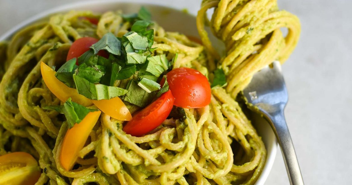 Avocado pasta recipe in a white pasta bowl with a glass of white wine. There is avocado pasta twirled around a fork on the edge of the bowl.