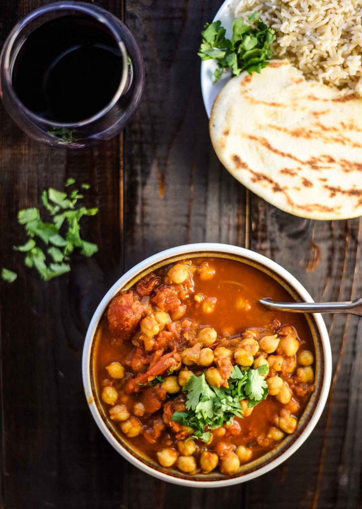 Vegan chana masala with naan, rice, and a glass of red wine.