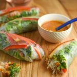 Fresh vegan spring rolls on a wooden cutting board with a small white bowl of peanut sauce. One of the spring rolls is cut open and there are some drops of peanut sauce drizzled on the cutting board.