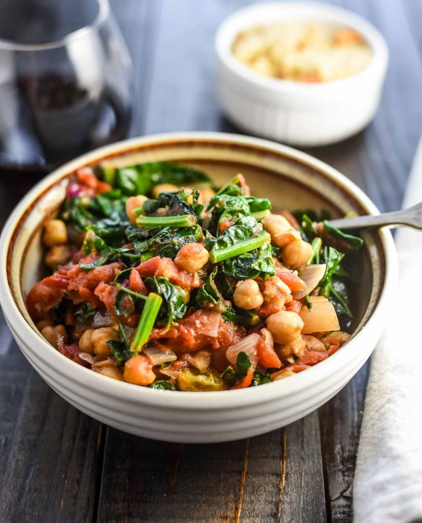 Moroccan chickpea stew in a white bowl with a spoon in the bowl. There is a glass of red wine behind the bowl.