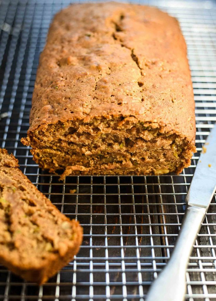 Vegan zucchini bread cooling on wire rack with one slice off of the end.
