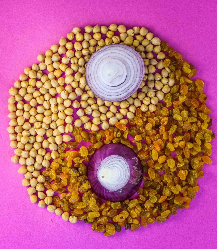 Moroccan chickpea stew ingredients of chickpeas, red onion, and golden raisins arranged in a yin yang.
