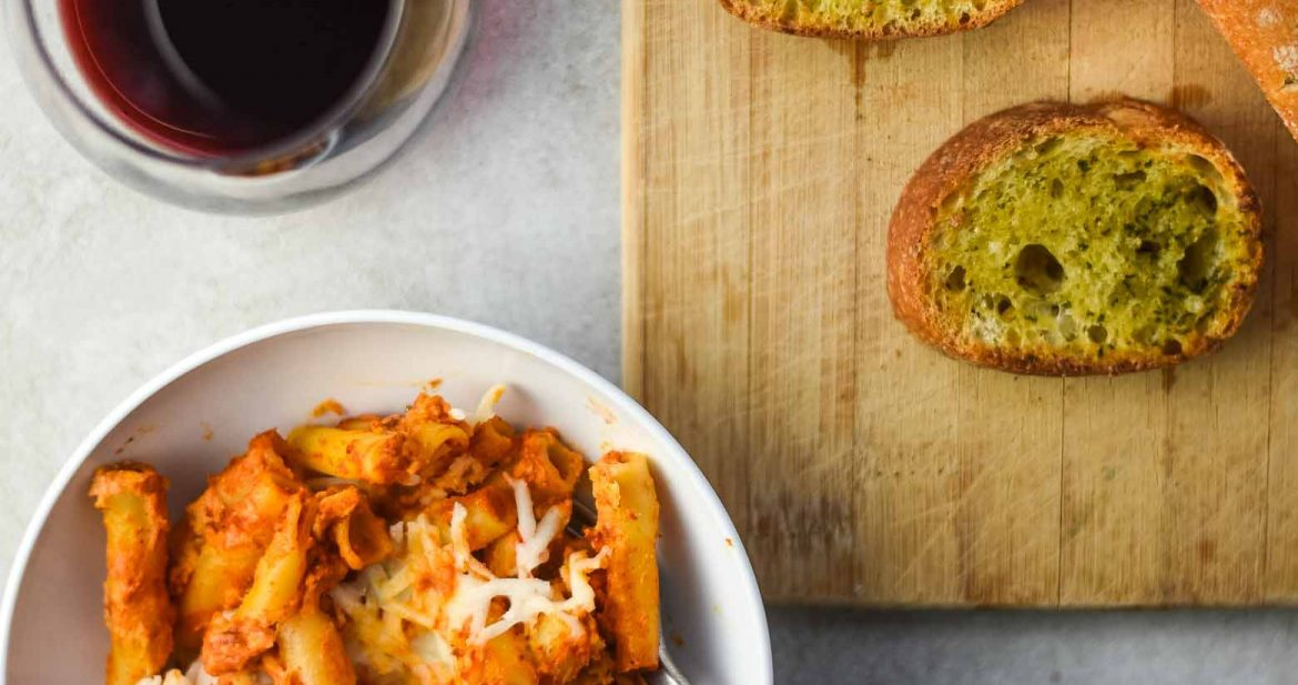 Vegan baked ziti with garlic bread and a glass of red wine.