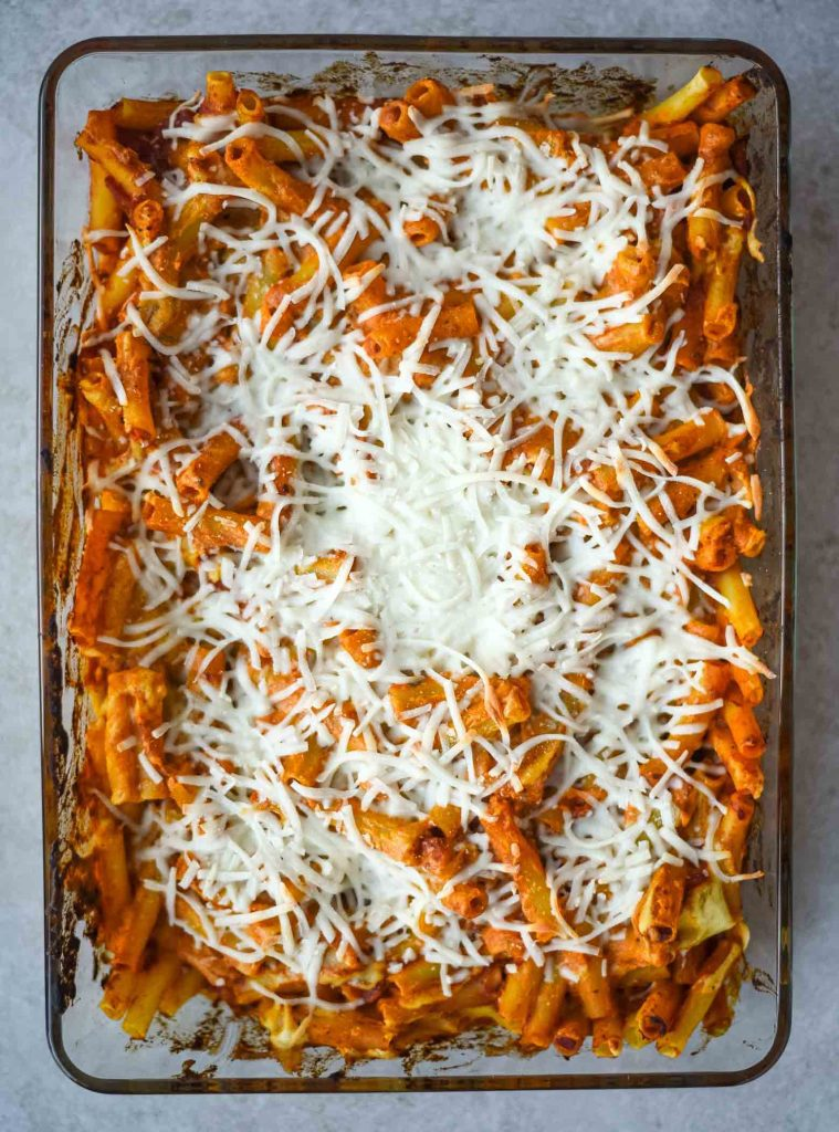 Vegan baked ziti in baking dish, fresh out of the oven with melted cheese.