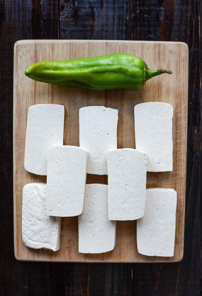 Tofu and anaheim pepper on cutting board. Ingredients for sofritas recipe.