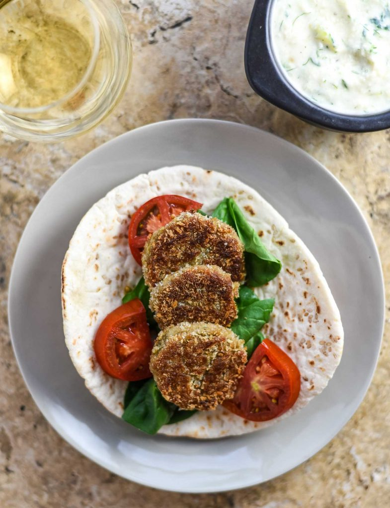 Vegan falafel in a pita bread with fresh veggies and a glass of white wine.