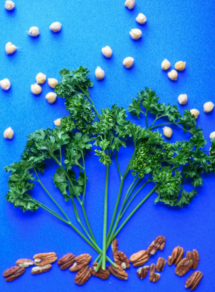 Vegan Falafel ingredients on a blue background - fresh parsley, chickpeas, raw pecans.