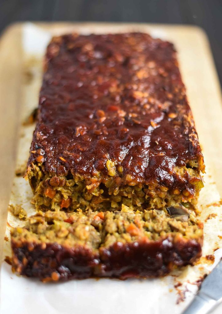 Vegan lentil loaf with veggies. Sitting on a cutting board, with a slice tipped towards the camera.