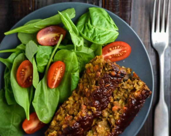 Vegan lentil loaf on blue plate with small spinach salad. There is a glass of white wine and a fork sitting nearby.