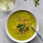 Vegan broccoli soup in a white bowl with a glass of white wine. It is topped with cheddar cheese and parsley.