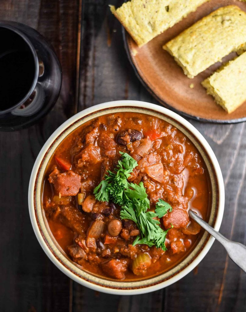 Vegan chili in a bowl with a glass of red wine and a plate of cornbread.