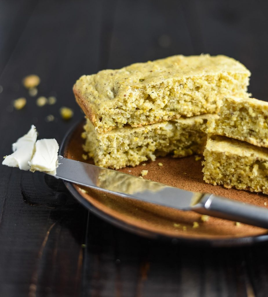Vegan cornbread with green chili slices on a brown plate with a knife with butter.