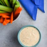 Vegan ranch dressing with carrot and celery sticks and a blue linen napkin.