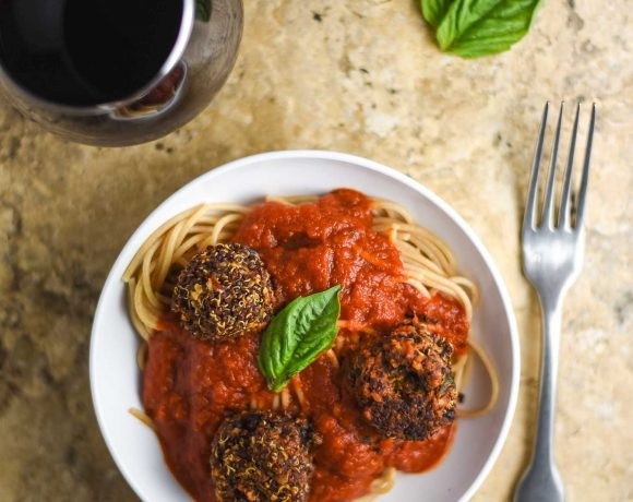 Vegan meatballs and spaghetti on a white plate with a glass of wine