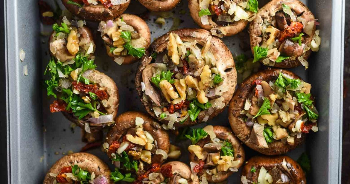 Vegan stuffed mushrooms in a baking pan, ready to be baked.