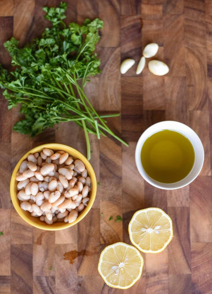Healthy white bean dip ingredients on a cutting board
