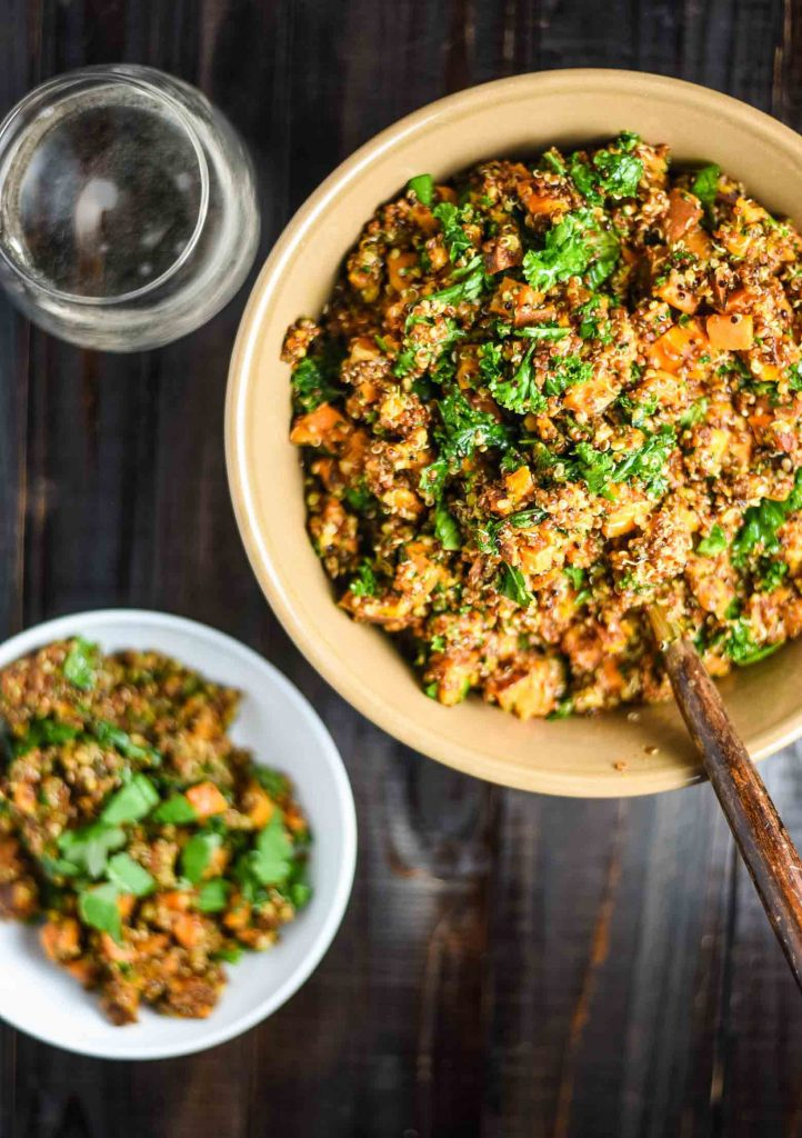 sweet potato quinoa salad in a bowl with a plate of it and a glass of white wine
