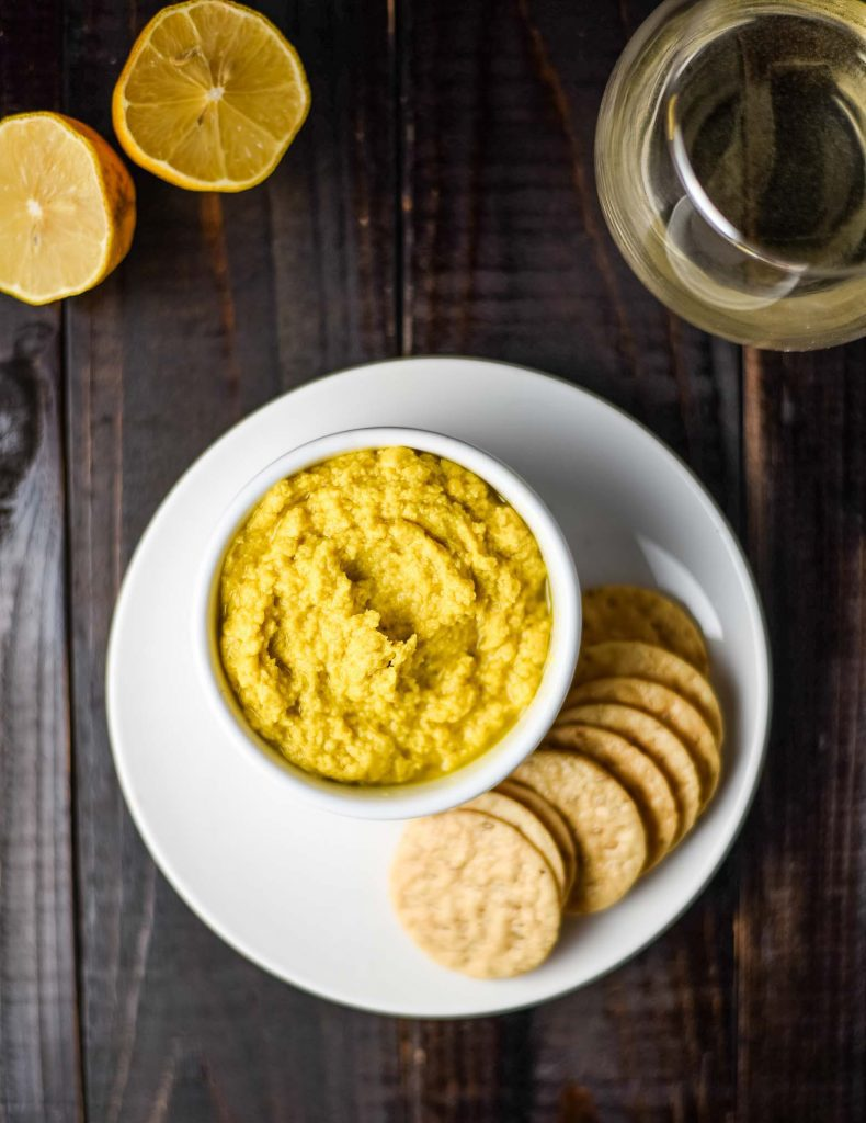 ginger turmeric hummus on a white plate with crackers and a glass of white wine