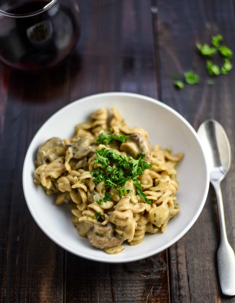 vegan mushroom stroganoff on a white plate with a spoon and a glass of white wine