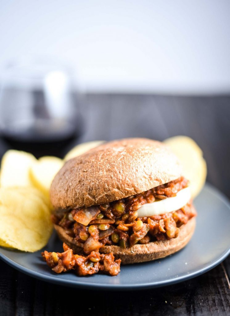 vegan sloppy joes on a blue plate with potato chips and a glass of red wine