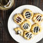 vegan thumbprint cookies with glaze on a white plate with a glass of wine
