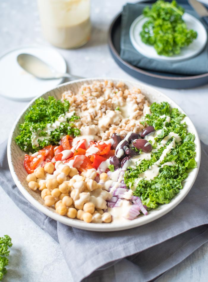 healthy mediterranean farro bowl in a white bowl with tahini sauce
