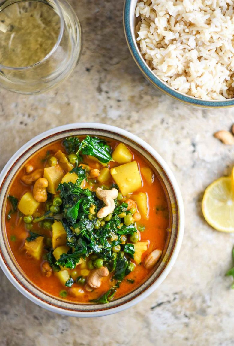 sweet potato curry with peas and kale in a bowl with a glass of white wine and a bowl of rice