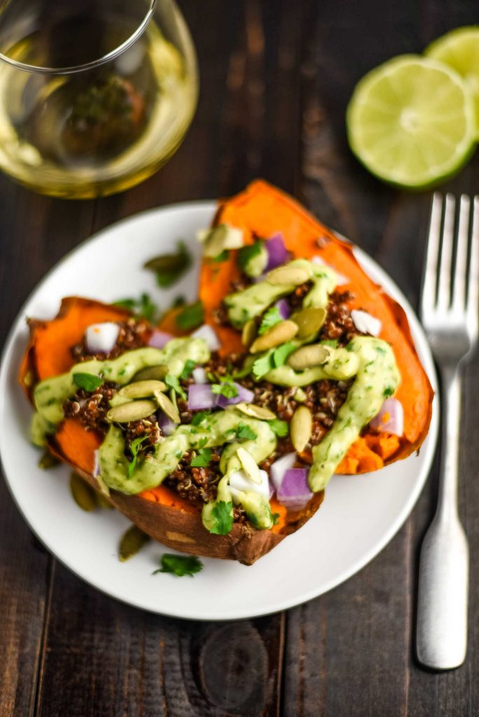 vegan stuffed sweet potatoes with quinoa, red onions, and avocado cilantro sauce